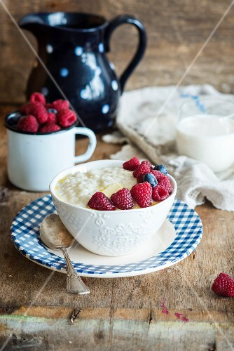Kascha (Russian rice porridge) with butter, raspberries blueberries and milk