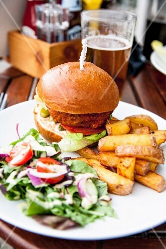 A vegan burger with chips and salad in a restaurant
