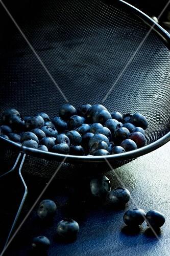 Blueberries in a black metal sieve