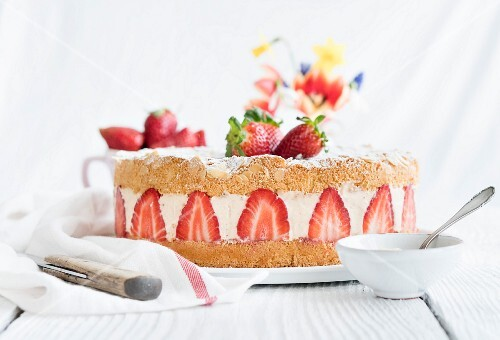 A whole strawberry cream cake on a table