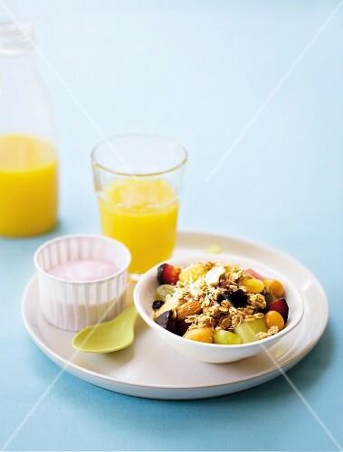 Breakfast muesli with fruit, yoghurt and orange juice