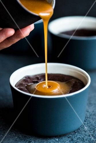 Caramel sauce flowing onto molten chocolate pudding