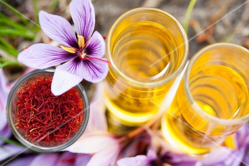 An arrangement of saffron threads, saffron flowers and dissolved saffron in glasses