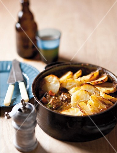 Beef casserole topped with sliced potatoes in a casserole dish