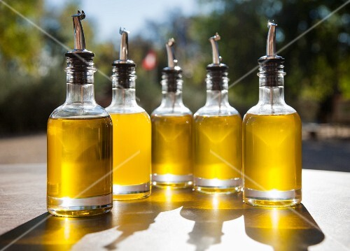 Olive oil in bottles with pourers on an outdoor table