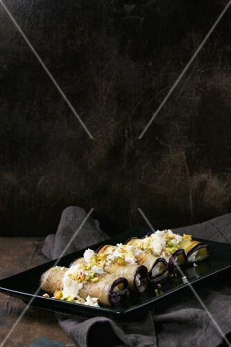 Aubergine rolls with ricotta, garlic, cheese sauce and pistachio nuts