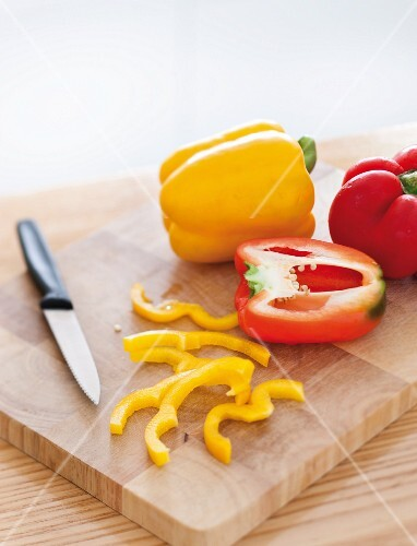 Yellow and red pepper on a chopping board