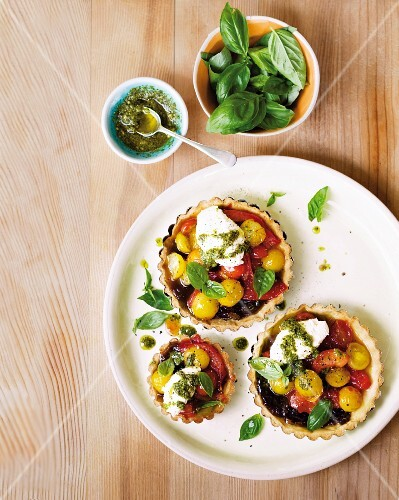 Tartlets with caramelised tomatoes, pesto, cream cheese and basil