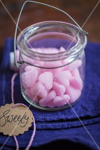 Pink sugar hearts in a glass jar with a written gift tag
