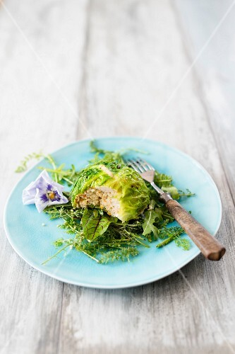 A ball of savoy cabbage stuffed with minced chicken on a bed of wild herb salad