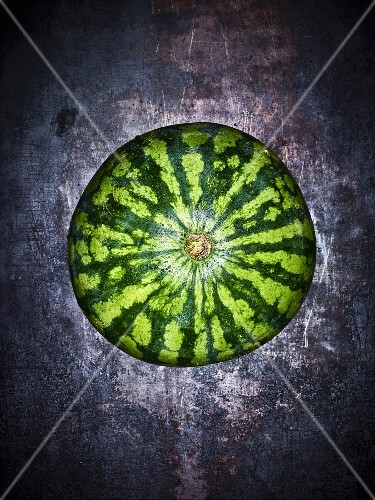 A watermelon on a grey background (seen from above)