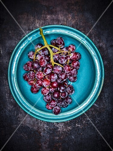Red grapes on a blue plate against a grey background