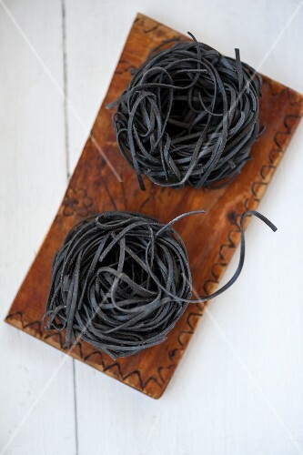 Two pasta nests made of black sepia pasta on a wooden board