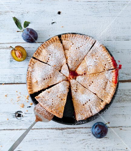 A sliced plum pie dusted with icing sugar
