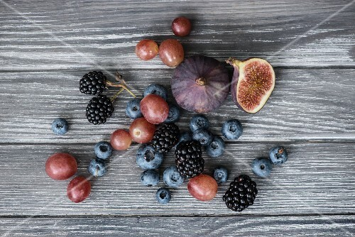 Blackberries, blueberries, blackcurrants, grapes and figs on a wooden surface