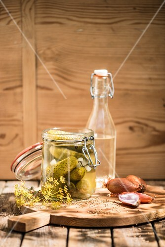 Gherkins in a preserving jar, vinegar, shallots, mustard seeds and dill on a wooden board
