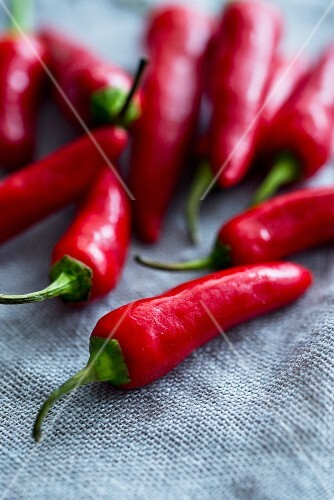 Fresh red chilli peppers on a fabric surface