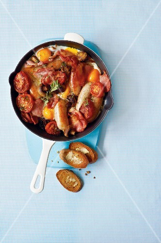 A hearty breakfast with sausages, eggs, bacon, tomatoes and mushrooms in a pan