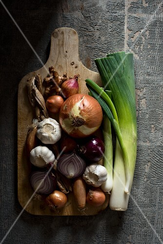An arrangement of onions, garlic and leeks on a chopping board (seen from above)