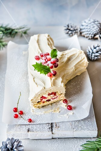 A white chocolate Yule log for Christmas with redcurrants and holly