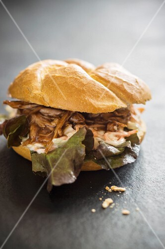 A pulled pork sandwich with oak leaf lettuce