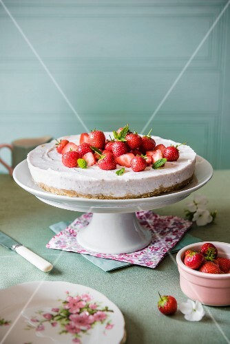 Strawberry cheesecake on a cake stand with fresh strawberries and mint