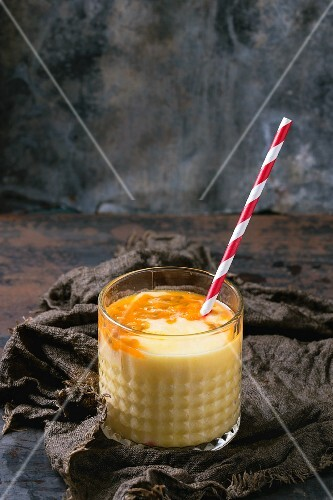 A glass of mango & passionfruit milkshake with a straw