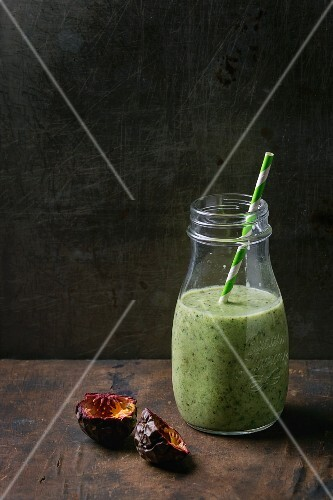 A bottle of kiwi & passionfruit milkshake with a straw on a wooden surface