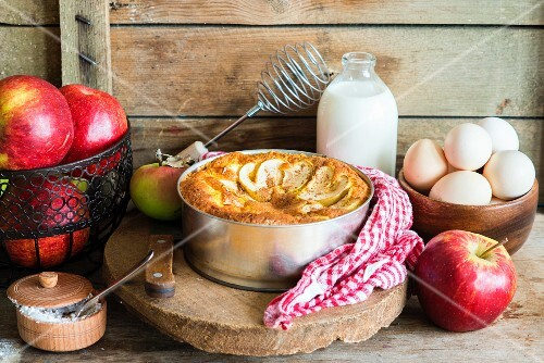 A sponge apple cake in a cake tin surrounded by ingredients
