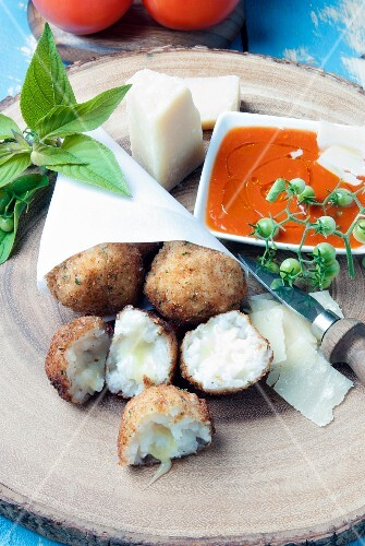 Arancini with cheese in a paper bag, served with tomato sauce and Parmesan