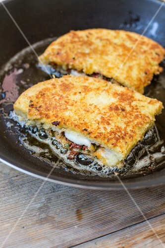Mozzarella in carrozza (an Italian fried mozzarella sandwich) being fried in a pan