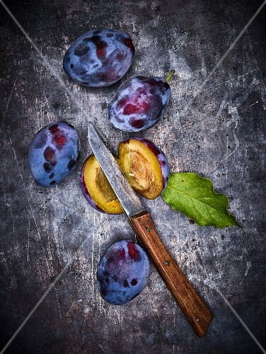 Whole and halved plums with a knife on a metal surface