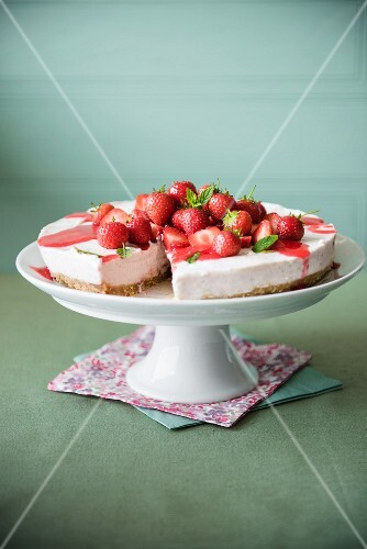 Strawberry cheesecake with strawberry sauce on a cake stand