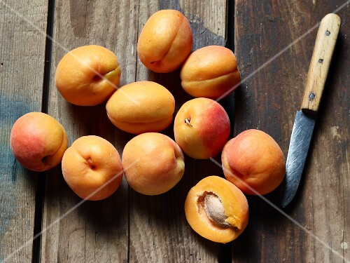 Fresh apricots with a kitchen knife on a wooden surface