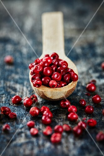 Red peppercorns on a wooden spoon