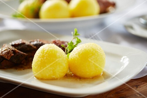 Potato dumplings as a side dish served with roast goose