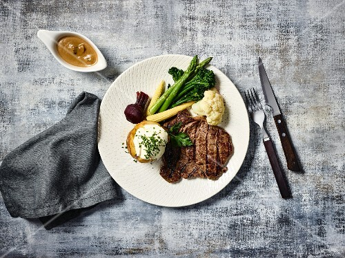 Beef steak with baked potato and vegetables