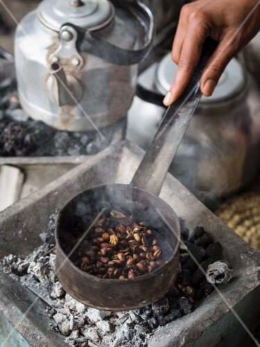 A woman roasting green coffee beans at a traditional coffee ceremony in Ethiopia