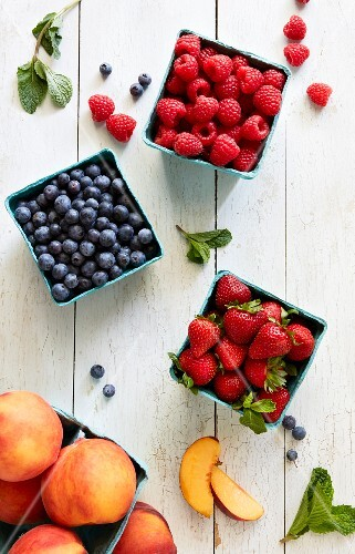 Raspberries, blueberries, strawberries and nectarines in cardboard boxes