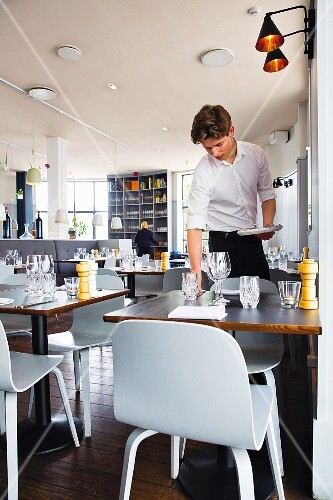 A waiter setting a table at the restaurant Almanak in Copenhagen, Denmark