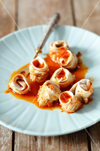 Herring rolls with onion and a spicy tomato sauce