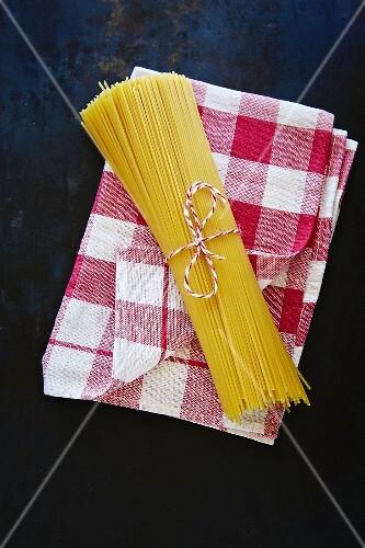 A bunch of spaghetti on a checked tea towel