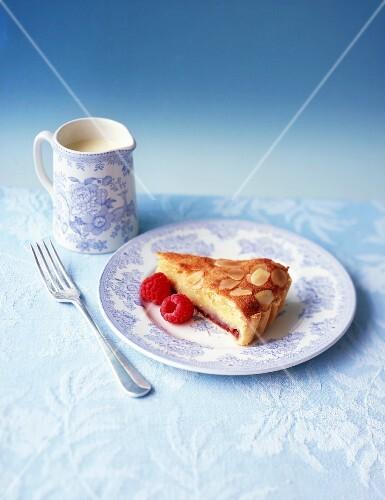 A slice of Bakewell tart with raspberries