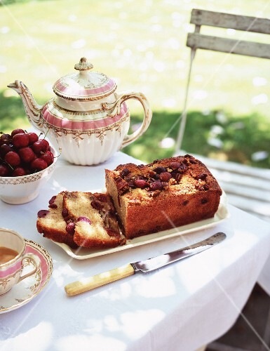 A coffee table with cherry cake in the garden