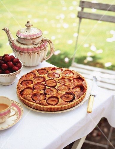 A coffee table in the garden with plum cake