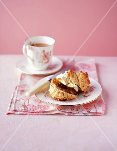 A scone with jar, clotted cream and a cup of coffee