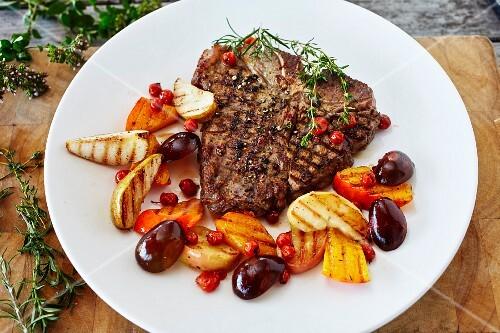 A T-bone steak with glazed fruits and pumpkin