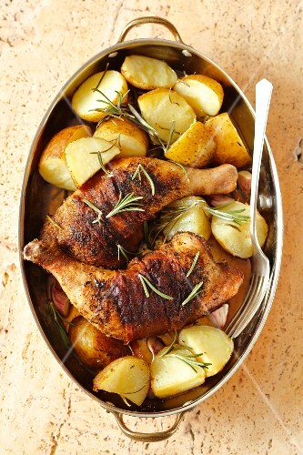Baked chicken thighs wrapped in prosciutto with roast potatoes and rosemary