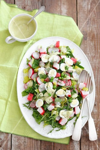 Salad with surimi, quail eggs, radishes, peas and mayonnaise dressing
