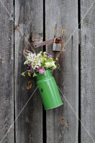 Flowers in old enamel milk churn on wooden door